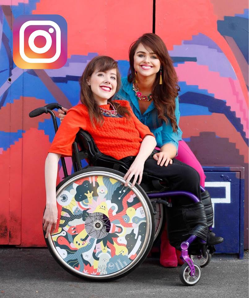 Two women with dark hair, one in a wheelchair.