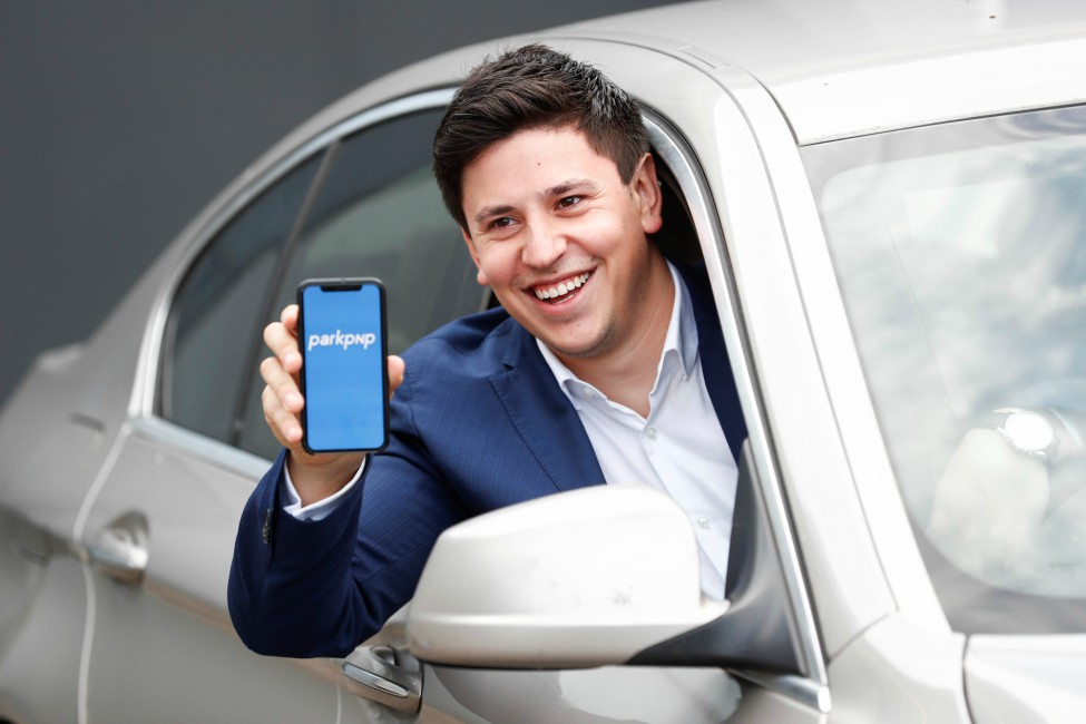 Man in blue jacket holding phone out of car.