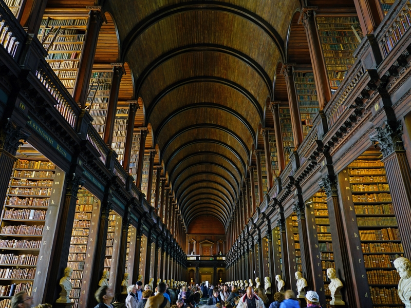 People walking around inside library at Trinity College Dublin.