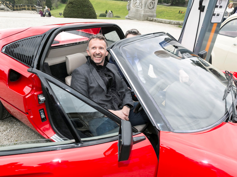 Smiling man in driving seat of an electrical Ferrari.