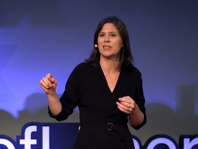 Woman in black dress talking on a stage at a TED talk.