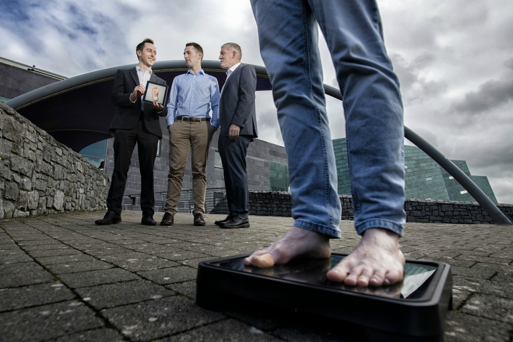 Man on scales in front of three men.