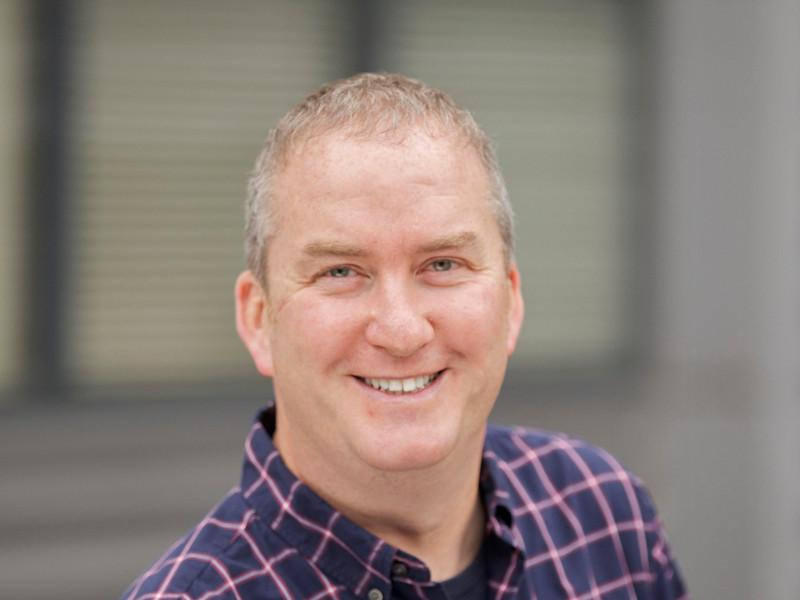 Smiling man in plaid shirt.