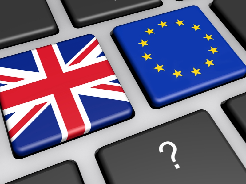 UK flag and EU flag on keyboard with a question mark.