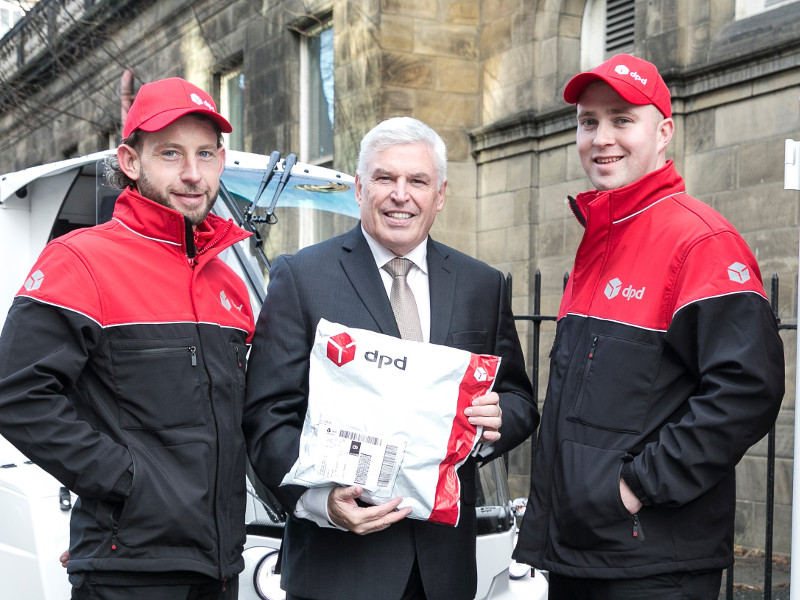 Two men in courier uniforms with one man in a suit holding a parcel.
