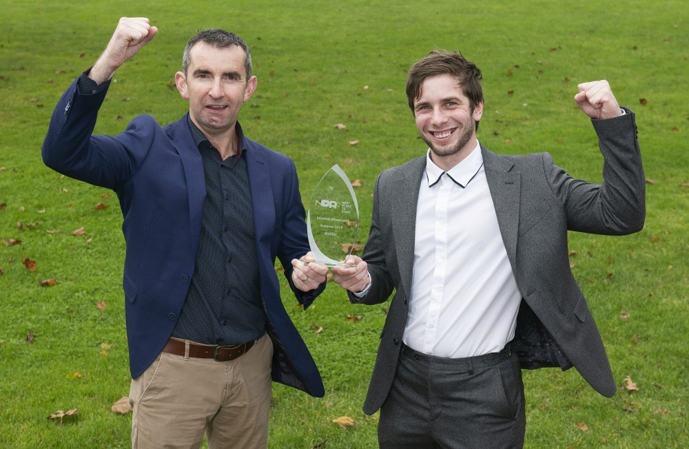 two men holding an award on a green field.