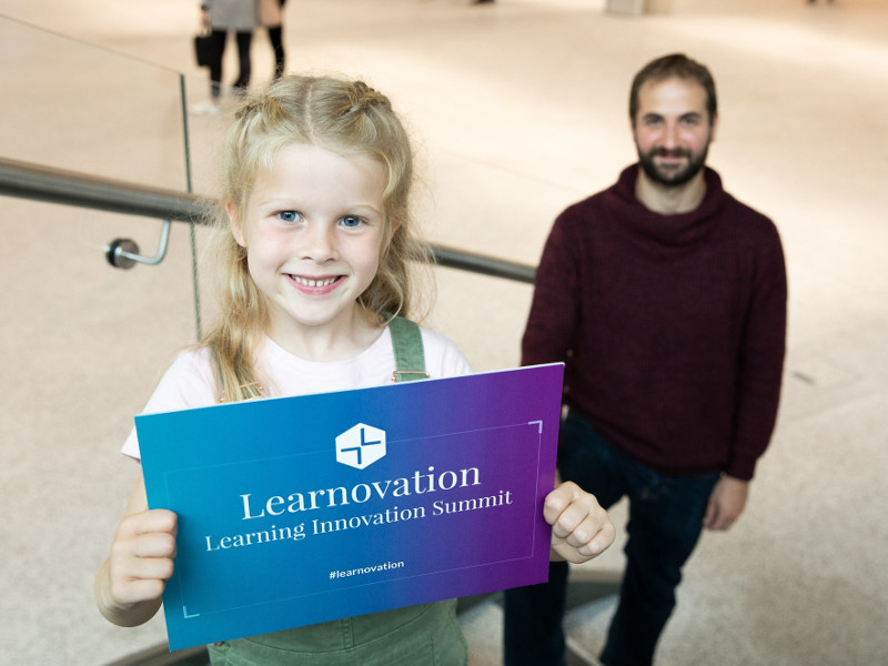 Blonde-haired girl holds a blue sign for Learnovate event with dark-haired man standing on steps in background.