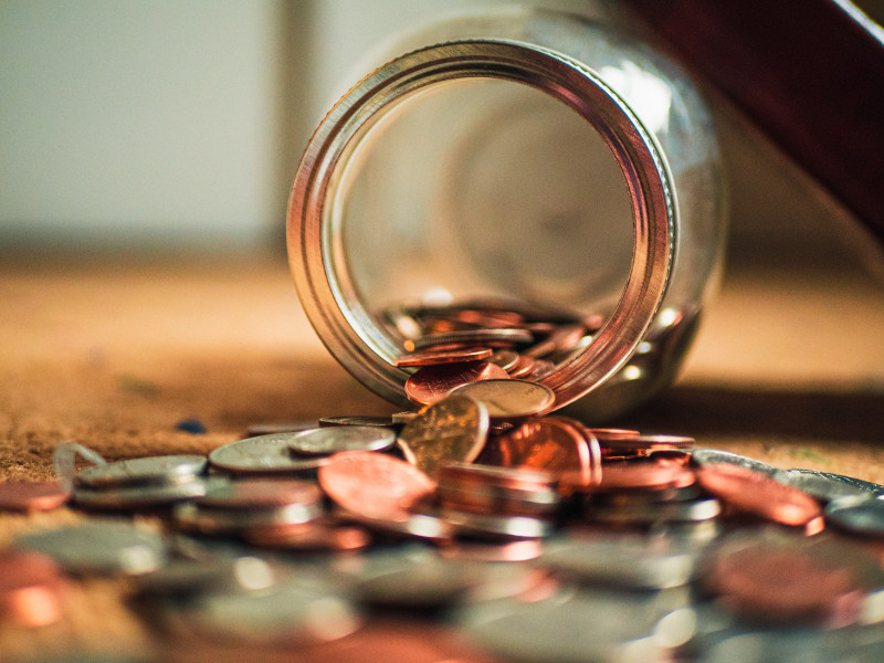 Picture of a jar on its side with coins flowing out of it.