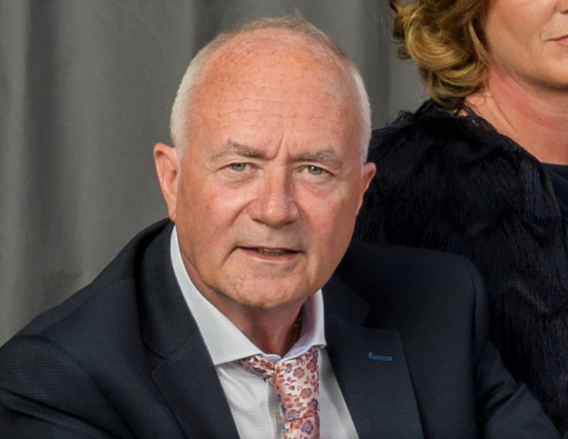 Dapper middle-aged man in dark suit and pink floral tie.