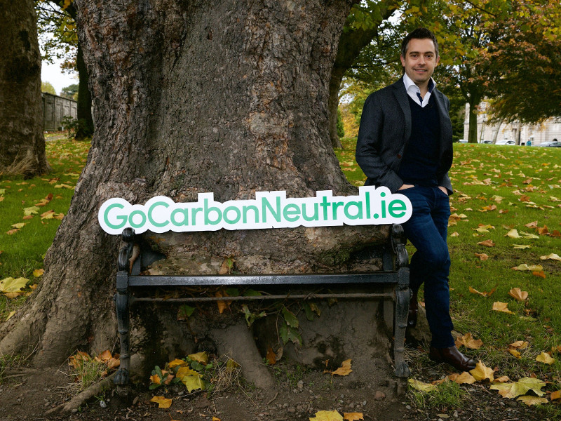 Man standing beside a tree with a sign saying Gocarbonneutral.ie.