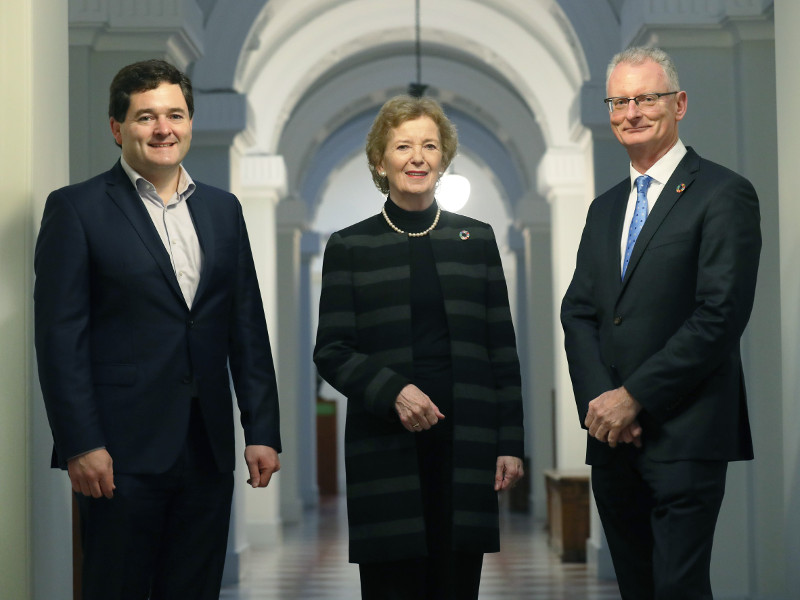Two men and a woman standing in a hallway.