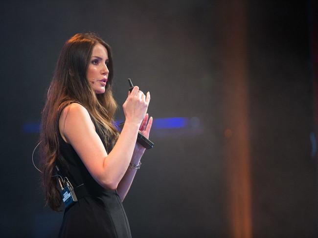 Woman in black dress talking on stage.