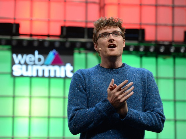 Man in glasses and woolly jumper on stage at Web Summit.