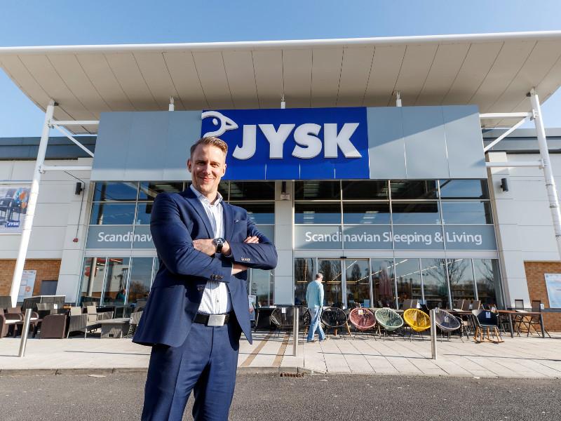 Man in blue suit standing outside JYSK store in Naas.