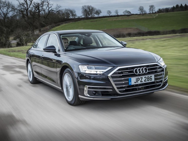 Electric audi saloon driving along a road.