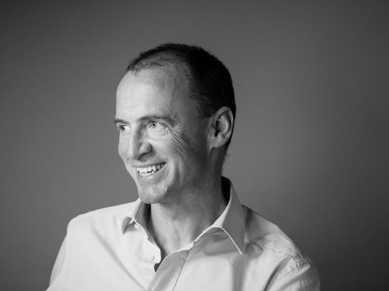 Smiling man in white shirt.