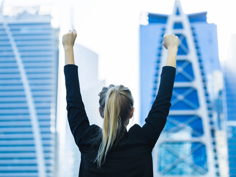 Blonde woman in business suit holds hands in air in jubilation.