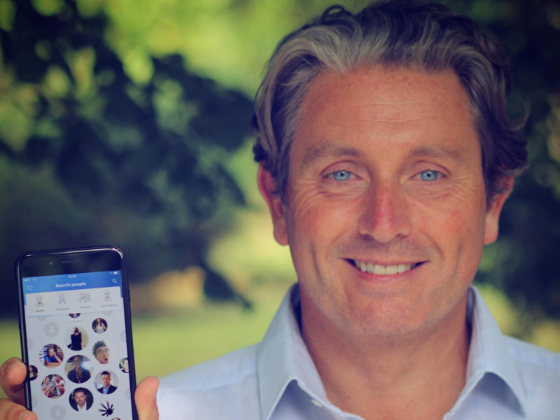 Smiling man with blue eyes holding a phone.