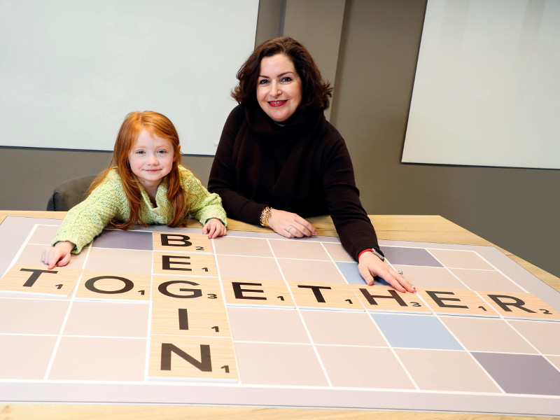 Woman in black sweater alongside young girl with red hair.