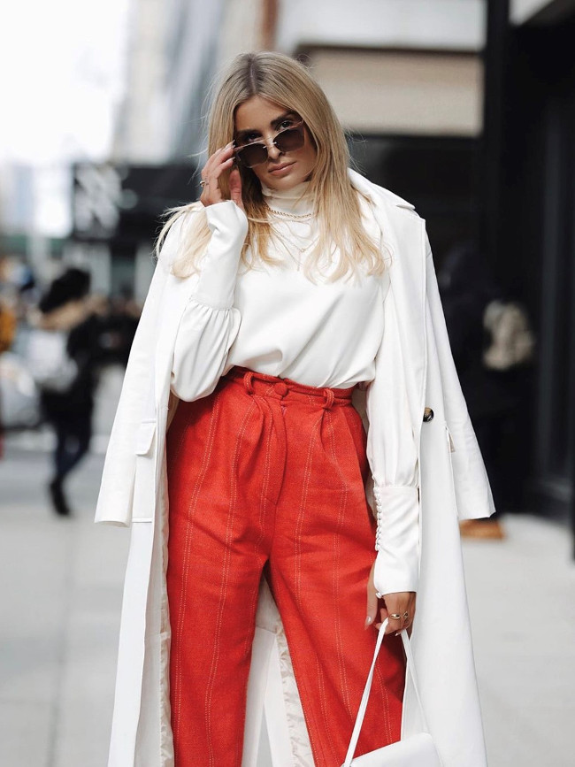 A model wearing a white coat and red trousers.