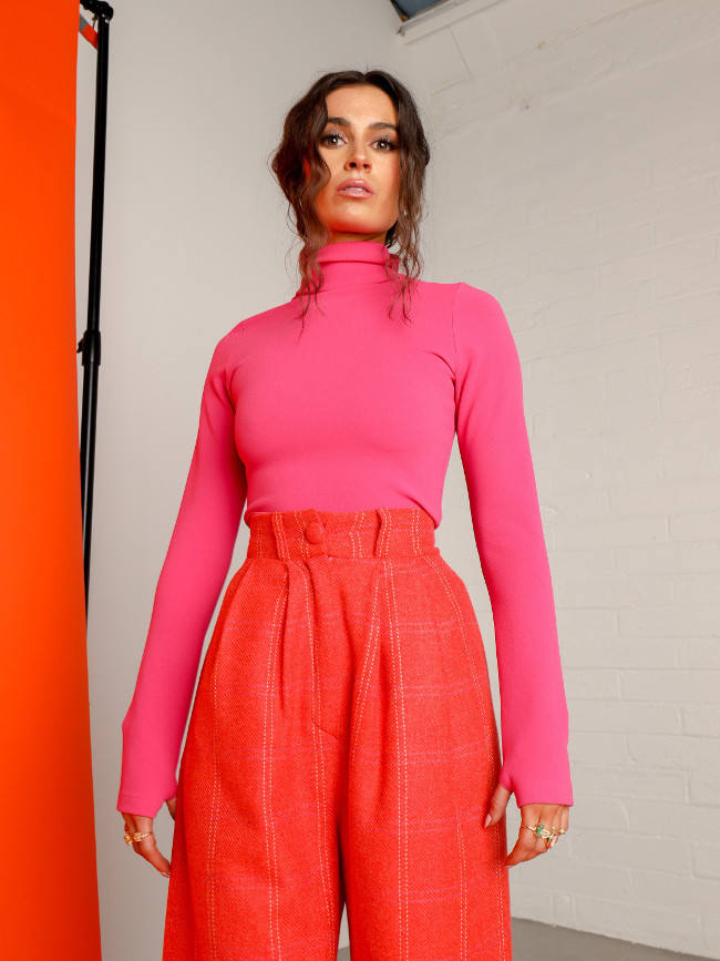 A model wearing pink jumper and red trousers.