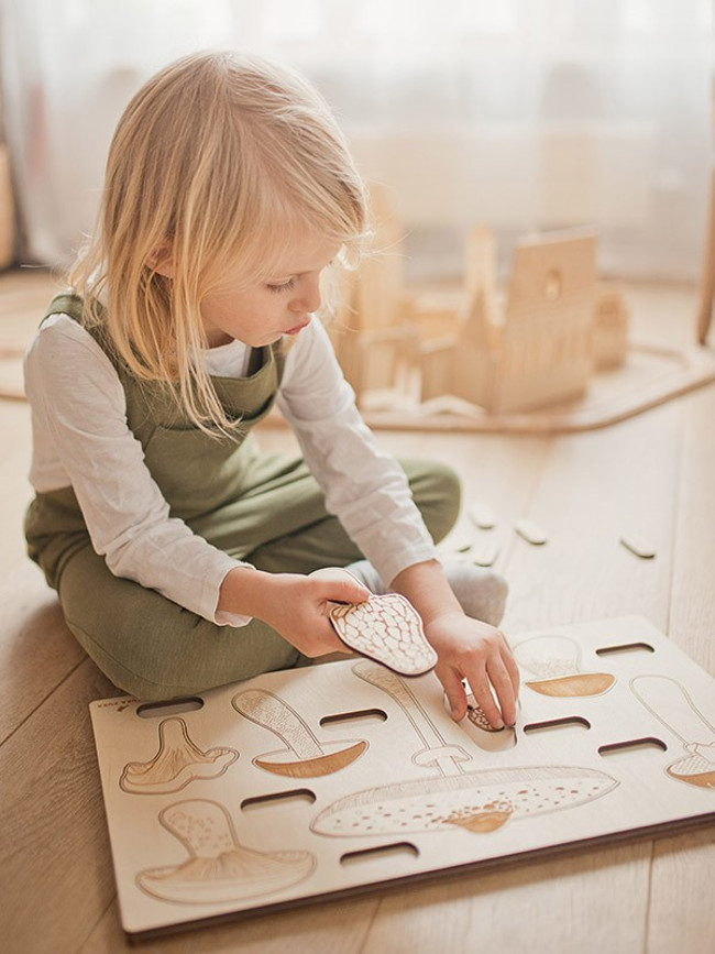 Young girl playing with a wooden puzzle.