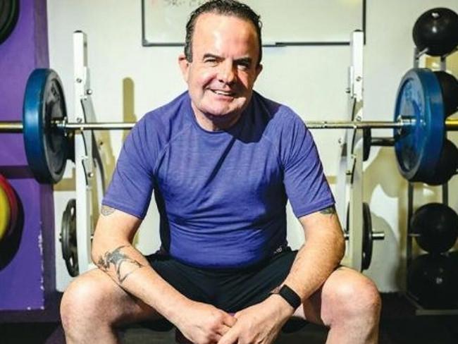 Man sitting on bench in gym.