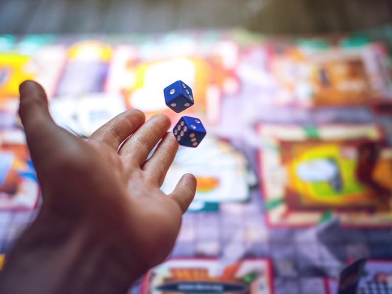 Man throws dice in board game.