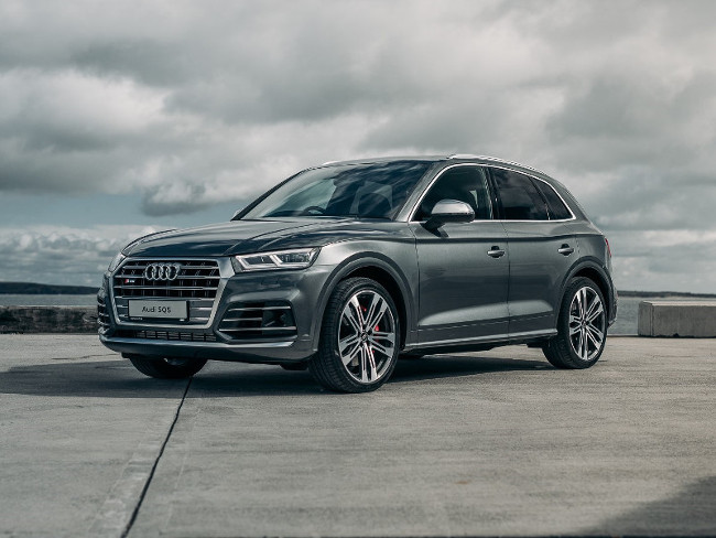 Grey Audi SQ5 parked by the sea.