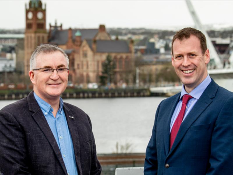 Two smartly dressed men standing beside a bridge in Derry.
