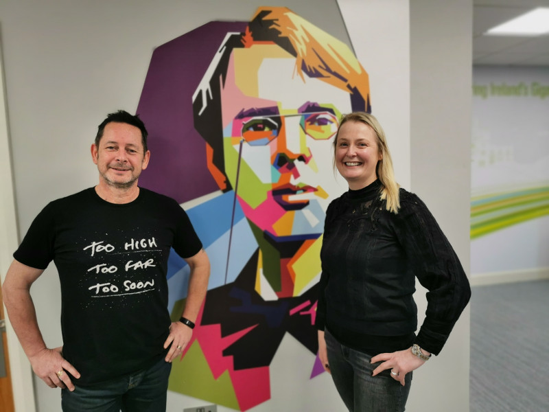Man and woman standing in front of a mural of William Butler Yeats.