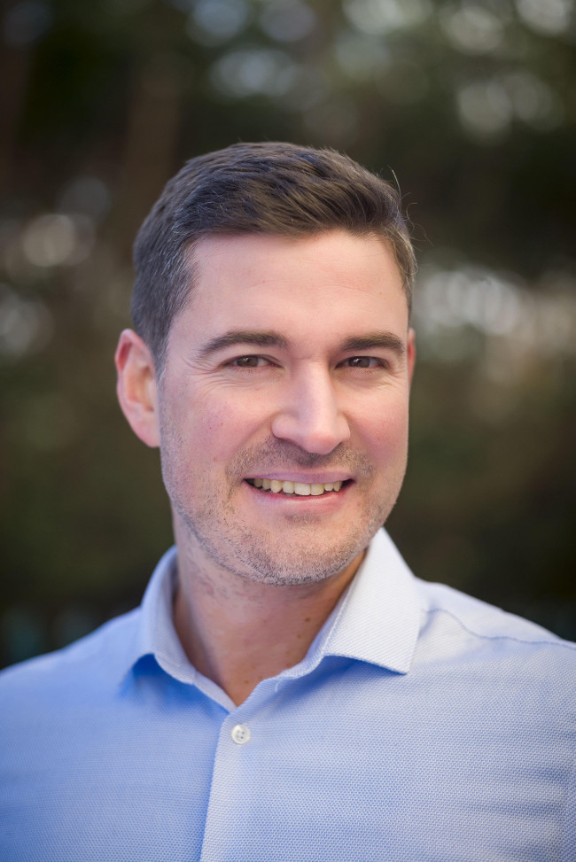 Smiling man in blue shirt.