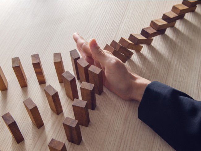 Hand stopping dominos.
