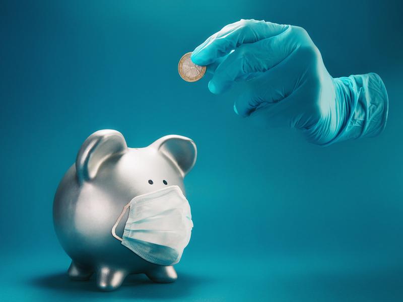 Silver piggy bank wearing a mask.