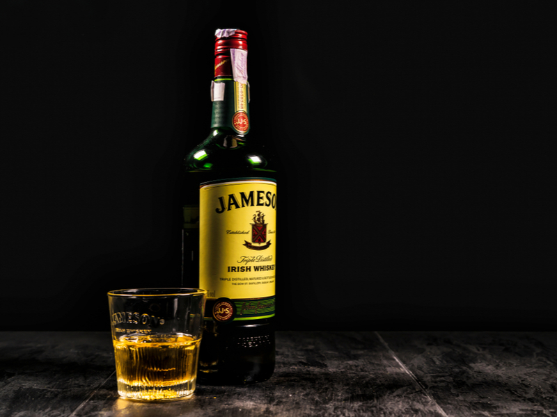 A bottle of Jameson beside a glass of whiskey.