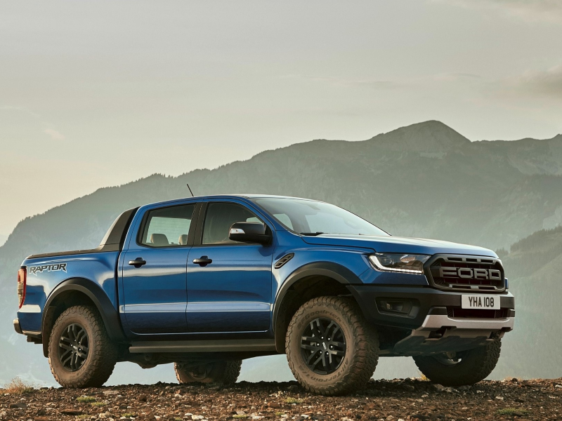 Blue Ford Raptor pick-up truck on a hill.