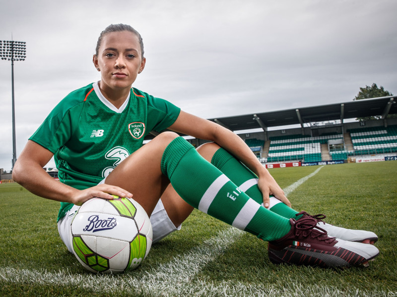 Woman in Ireland jersey sitting on a pitch.