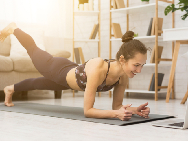 Woman exercising in front of a laptop.