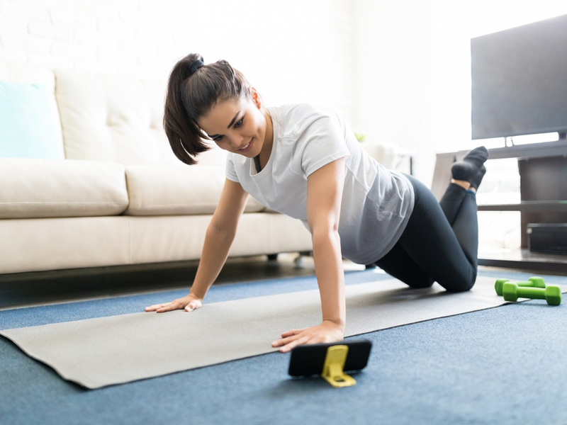 Young woman doing exercises with instructions from her smartphone.