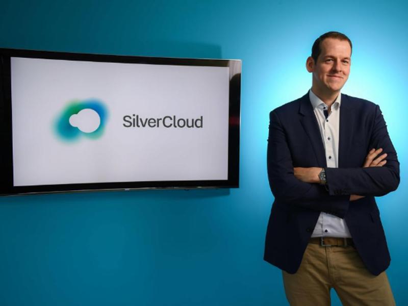 Man in navy jacket standing beside a screen with words SilverCloud on it.
