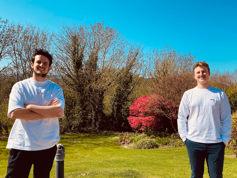 Two young men standing in a garden.