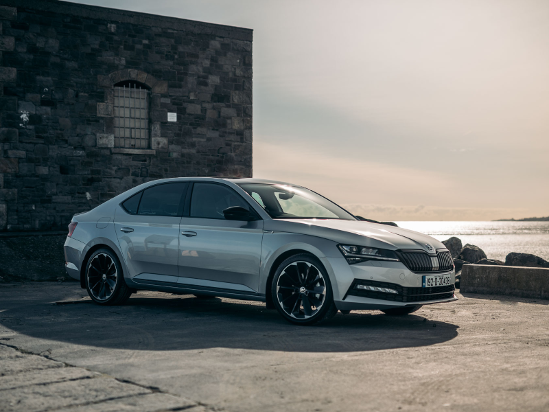Silver Skoda Superb on a harbour wall.