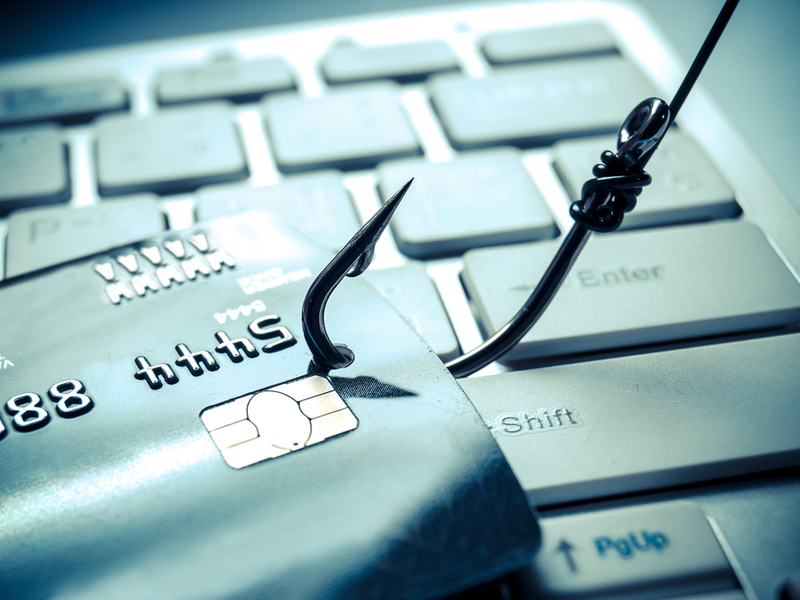 Image of a fishing hook going through a credit card on a keyboard.