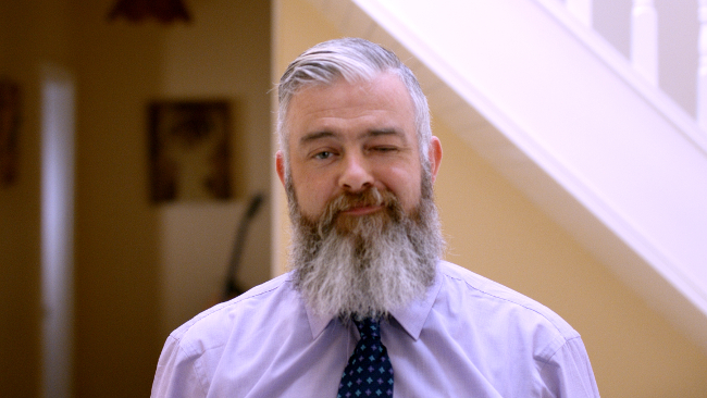 Grey-bearded man in shirt and tie.