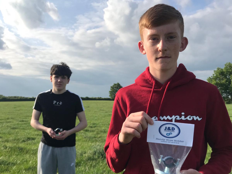 Two young students holding a product they invented.