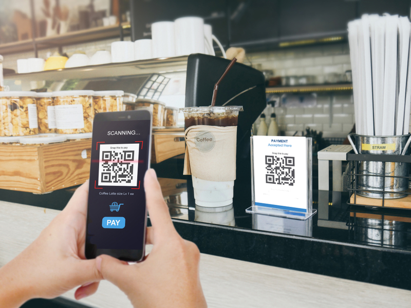 Person paying for coffee with a QR code in a shop.