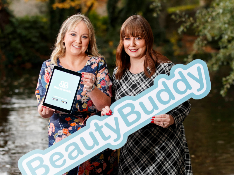 Two women holding a beauty buddy sign.