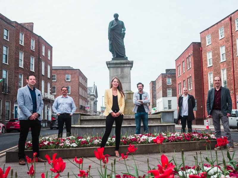 Group of people standing beside a statue in Limerick.