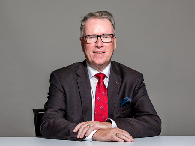 Well-dressed man in grey suit and glasses.