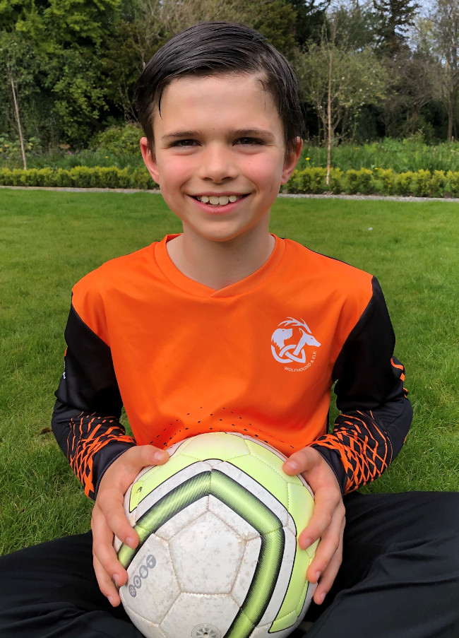 Young boy wearing orange and black football jersey.